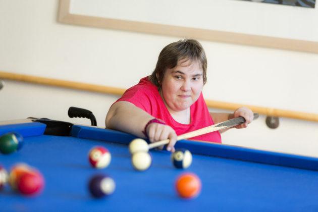 Eine Rollstuhlfahrerin spielt Billard