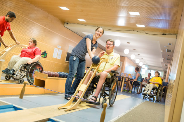 Rollstuhlfahrer auf der Kegelbahn