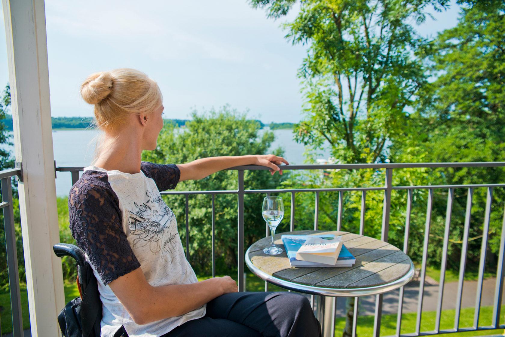 Eine Dame im Rollstuhl sitzt auf dem Balkon und guckt über den See