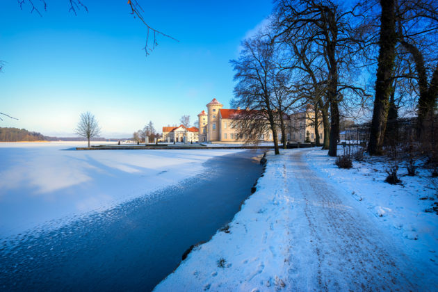 Verschneite Seepromenade mit Blick auf den zugefrorenen See